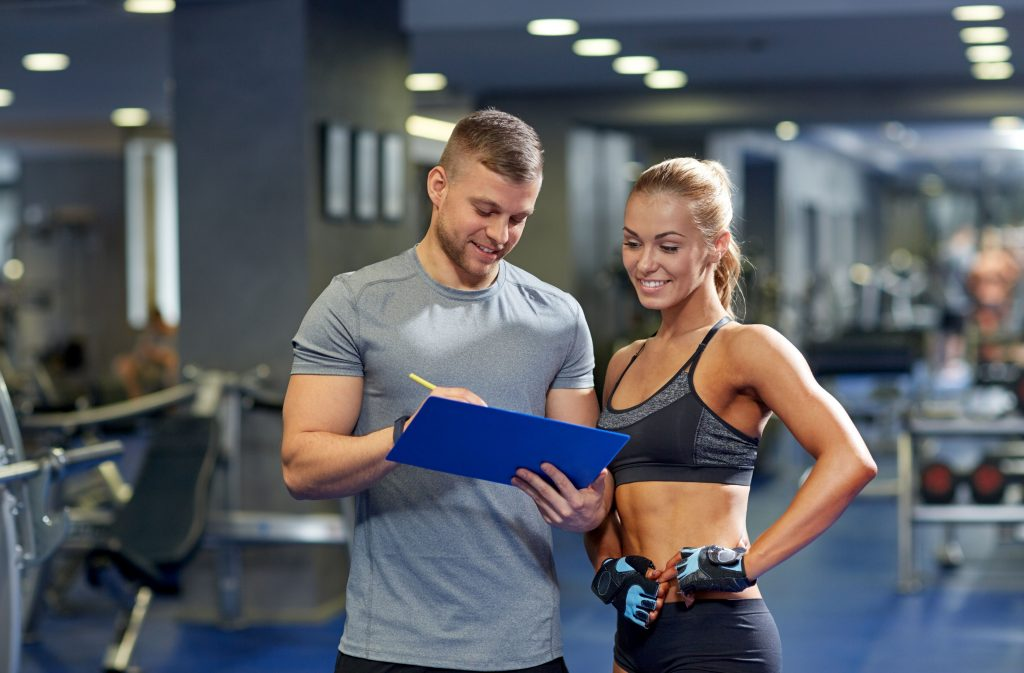 48507620 - fitness, sport, exercising and diet concept - smiling young woman and personal trainer with clipboard writing exercise plan in gym